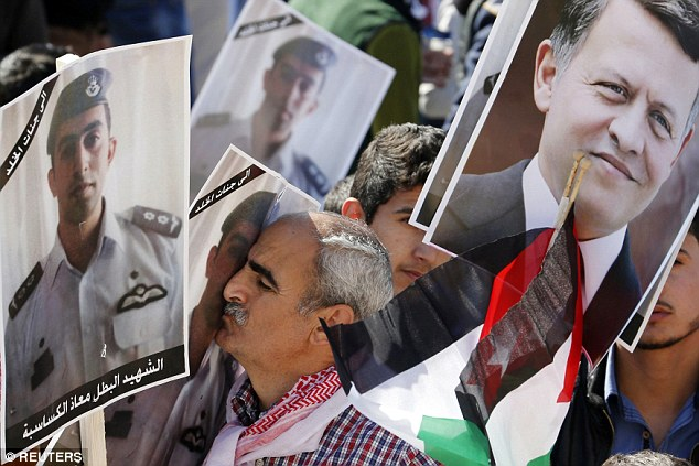 Rally: A Jordanian protester kisses a poster bearing the image of Jordanian pilot Moaz al-Kasasbeh during a rally to show their loyalty to King Abdullah and against the Islamic State
