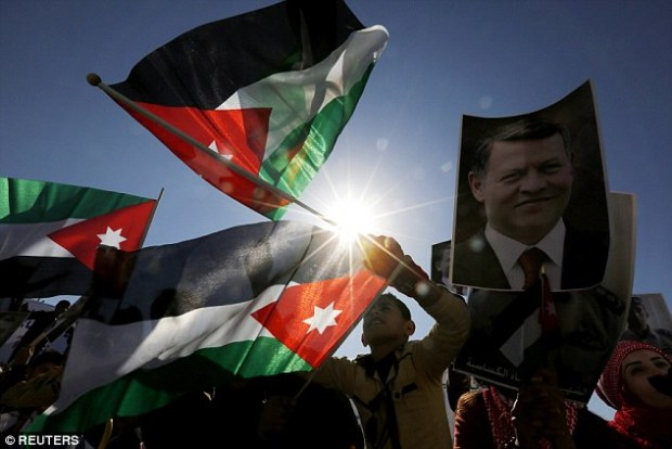 Jordanians hold up pictures of the King and murdered pilot Moaz al-Kasasbeh while chanting slogans during a rally today