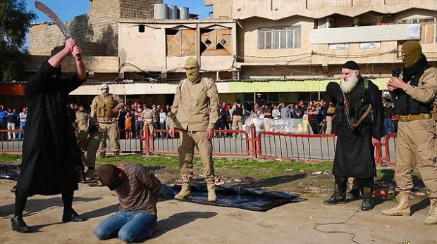 The photographs were revealed just five days after chilling new images emerged of three men being beheaded. The executioner stands with the sword poised above the man's head as a large crowd gathers to watch