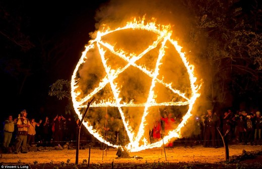 Worship: Participants dance before giant burning pentagrams before they pledge their souls to Satan