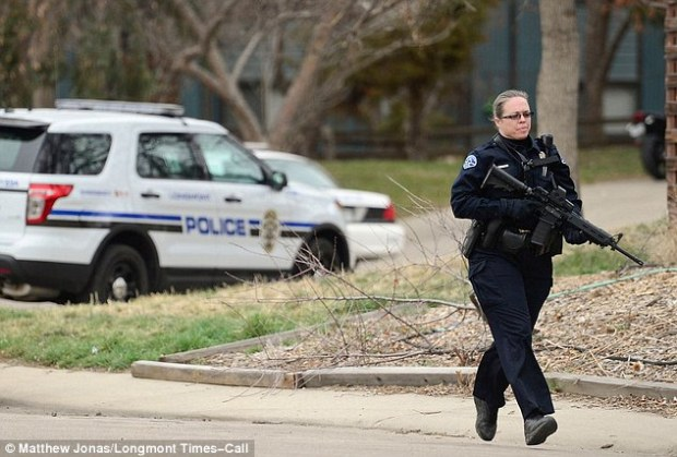 Investigation: Police say the 34-year-old woman who lives at the home stabbed the pregnant woman and 'removed' her baby. Seen here is a heavily-armed officer outside the property Wednesday afternoon