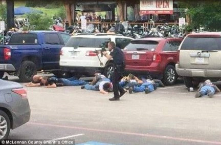 Gunfight: An officer is seen above wielding a rifle while bikers are kept on the ground during the confrontation. Witnesses who have been trained in firearms suggested that semi-automatic weapons dominated exchanges