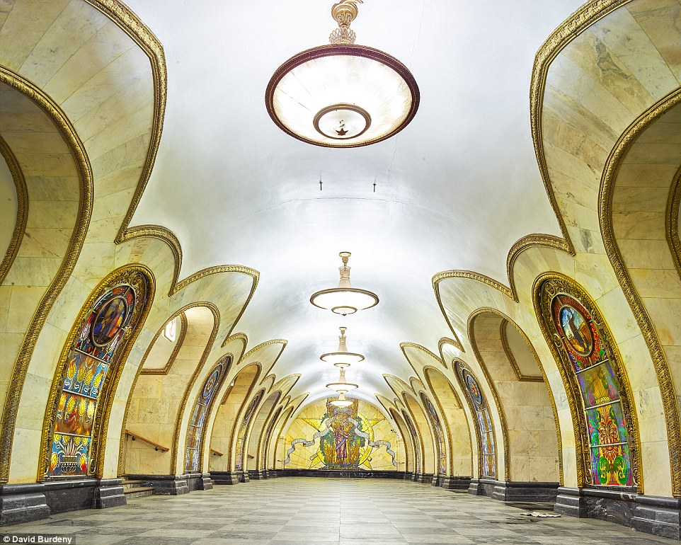 Rainbow-coloured scenes adorn the walls of the golden Novolobodskaya Metro Station, which looks more like a walkway in a castle than a tube station