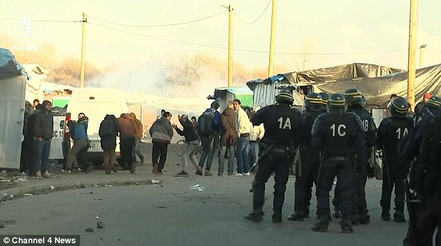 Migrants at the entrance to the Jungle camp in Calais throw stones at police after an outbreak of violence