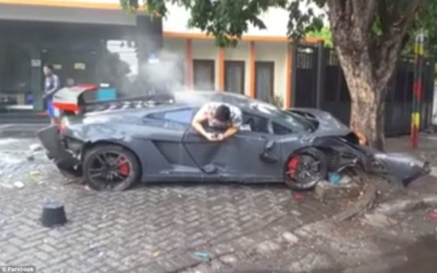 Footage has emerged showing a 24-year-old driver texting while hanging out of the window of his wrecked Lamborghini just moments after he allegedly mowed down three people