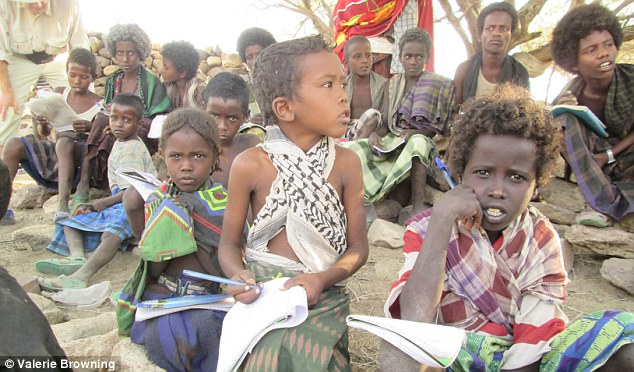 A group of young children sit in front of locals in the community where Ms Browning lives and works in Ethiopia