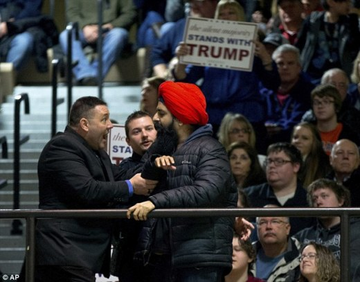 The protester wearing the red turban (above) was removed by security after interrupting Trump with another protester