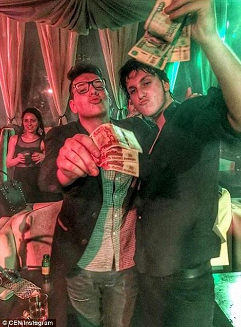 Two teenagers pictured on the Rich Kids of Russia Instagram page flash wads of cash inside a bar or nightclub