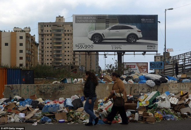 Two women walk past garbage piling up at a temporary dump in the town of Jdeideh, north east of the Lebanese capital Beirut, this week