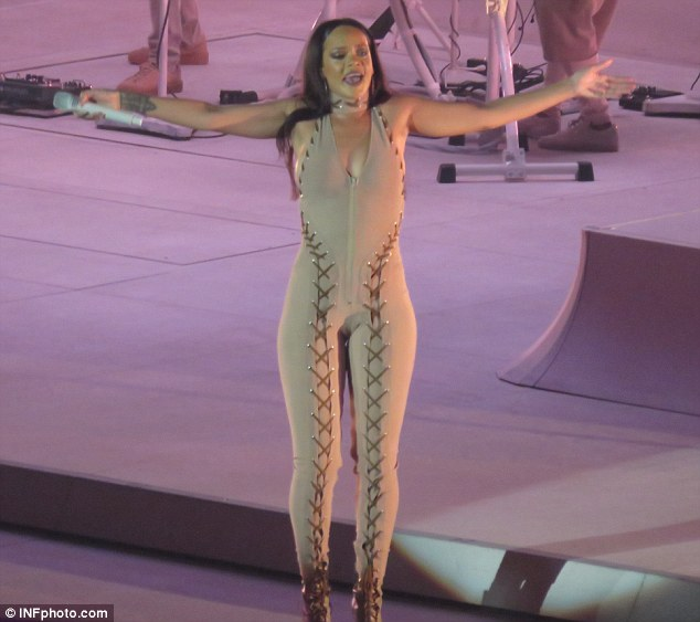 Racy:Sporting a camel coloured one-piece boasting a halterneck detail at the top, the catsuit extended into a cleavage flashing plunging neck