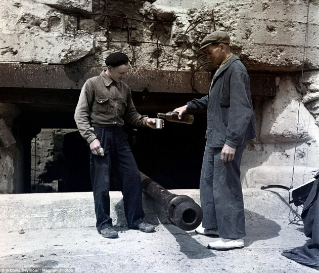 Two men share a drink beside one of the Nazi battlements constructed along the beach in order to try and repel the Allied invasion. Aware of the Allies intent to invade France, Hitler fortified the coast with guns and 50,000 troops placed in the control of general Erwin Rommell