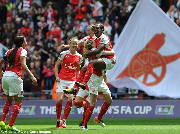 Danielle Carter (right) is held aloft by her Arsenal team-mates after she took the lead for Arsenal in the first half