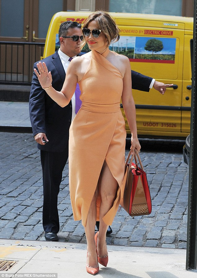 Pretty in peach: Jennifer Lopez slipped into a sleeveless dress featuring a triangular split down the middle which showed off her toned legs