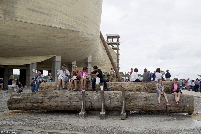 Visitors rest on giant logs at the Ark Encounter theme park. The towering replica of Noah's Ark stands behind them