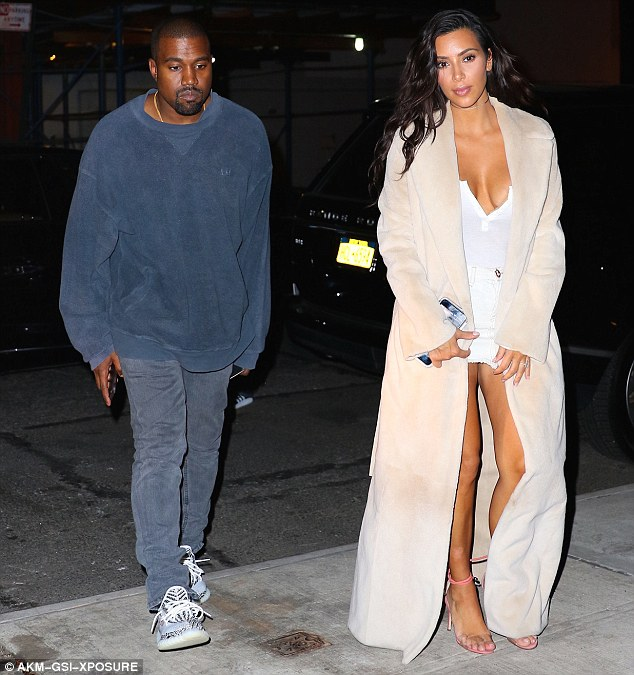 Stylish couple: Kanye's casual navy blue ensemble made for a rather low-key look in comparison to Kim's showstopping white outfit