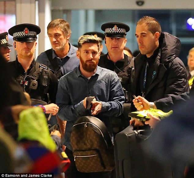 The Argentinian is flanked by police as he makes his way through Manchester Airport