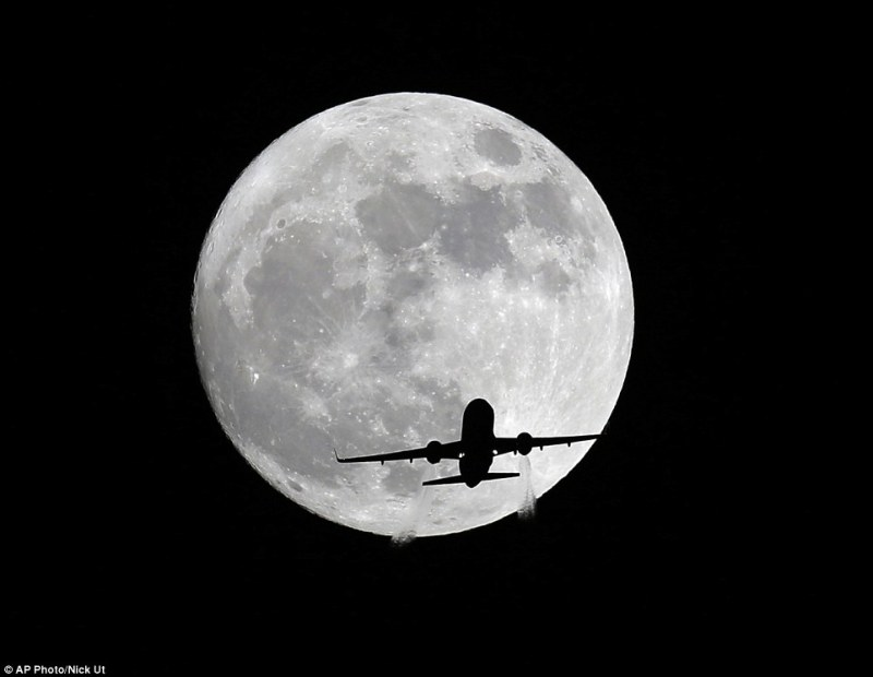 An American Airlines passenger plane passes in front of the moon, as seen from Whittier, California yesterday. Monday morning's supermoon will be the closet a full moon has been to the Earth since January 26, 1948