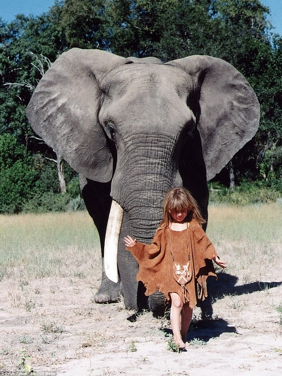 Tippi is pictured in front of 34-year-old elephant Abu in Botswana at the age of six