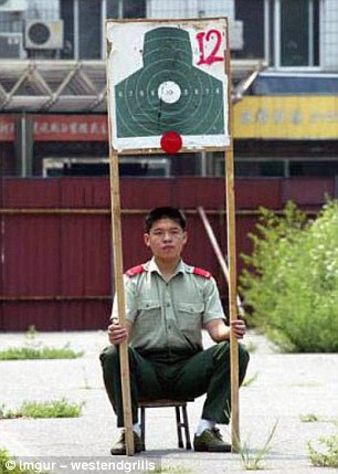 This uniformed employee from an unknown country appears to be holding a shooting board for target practice aloft above his head