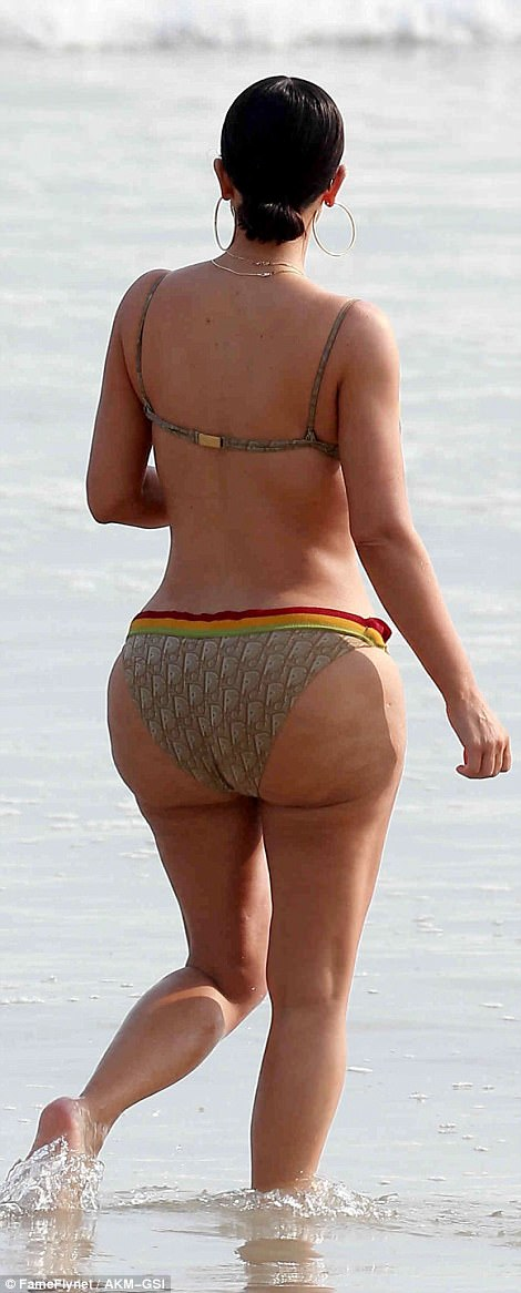 Booty-ful! Busting out of a skimpy bikini, Kim's body confidence was clear as she sashayed along the sand with her pals