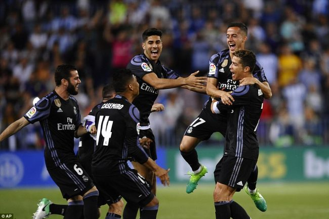 Real Madrid secured the La Liga title after a hard fought 2-0 victory over a spirited Malaga side