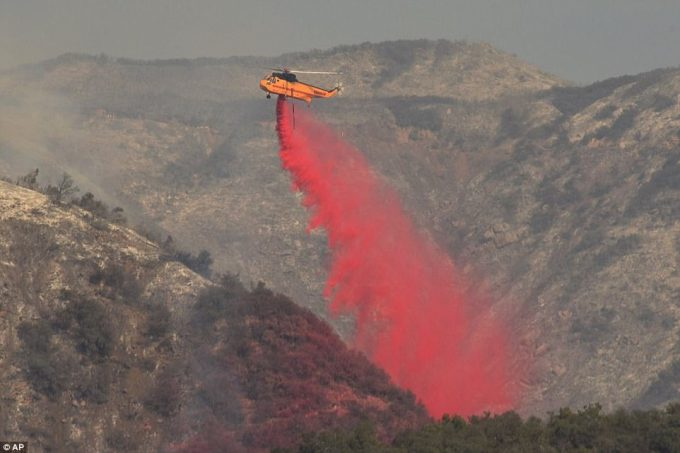 A helicopter drops fire retardant onto a hillside on Friday in San Ysidro Canyon in Montecito