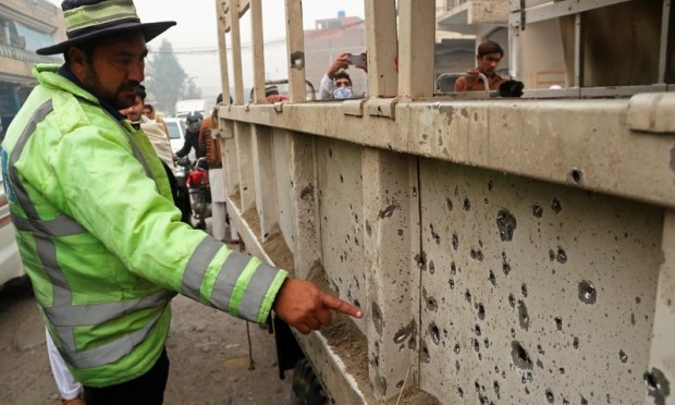 A police officer inspects security forces truck after an IED blast in Peshawar. ─AFP