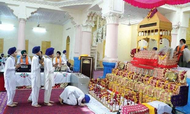 Sikh children worship at the historical Bhai Beba Singh temple at Hashtnagri, Peshawar, on Wednesday. — Photo by Shahbaz Butt
