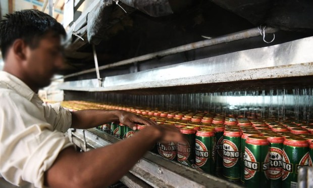 In this photograph taken on June 28, 2016, a worker checks a line of beer cans at the Muree Brewery Company in Rawalpindi. ─ AFP