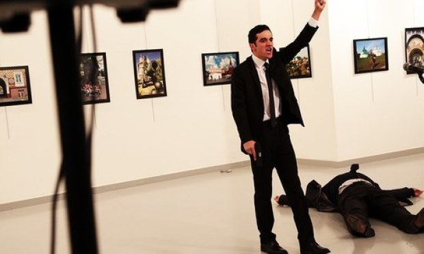 A man gestures near to the body of a man at a photo gallery in Ankara. -AP