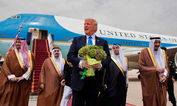 US President Donald Trump (C) holds a bouquet of flowers upon being welcomed by Saudi King Salman bin Abdulaziz al-Saud (R) during the former's arrival at King Khalid International Airport in Riyadh on May 20. ─ AFP