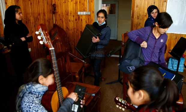 Members of the Zohra orchestra bring instruments to a class before a rehearsal. ─ Reuters
