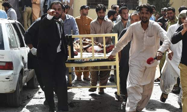 Lawyers and local media personnel carry a bed to move the body of a news cameraman after the explosion.— AFP