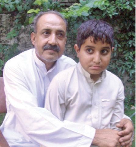 Sardar Yousafzai with his ailing son Zaland. — Dawn