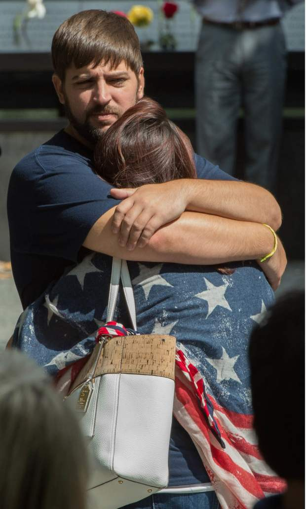 Family members embrace during the 15th Anniversary of September 11 at the 9/11 Memorial and Museum, in New York.  — AFP