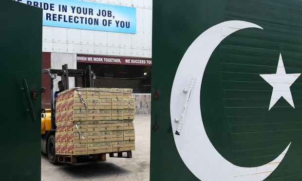 In this photograph taken on June 28, 2016, a worker uses a fork-lift truck to manoeuvre boxes of non-alcoholic malt bottles at the Muree Brewery Company in Rawalpindi. ─ AFP