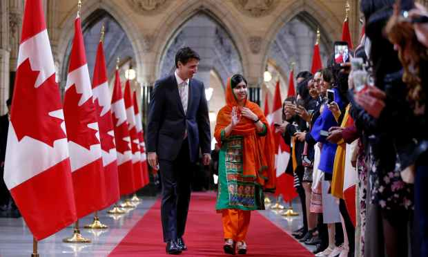 Justin Trudeau walks with Malala Yousafzai in the Hall of Honour on Parliament Hill. —Reuters