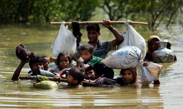 A Rohingya family reaches the Bangladesh border after crossing a creek of the Naf river on the border with Myanmmar, in Cox's Bazar's Teknaf area. —AP