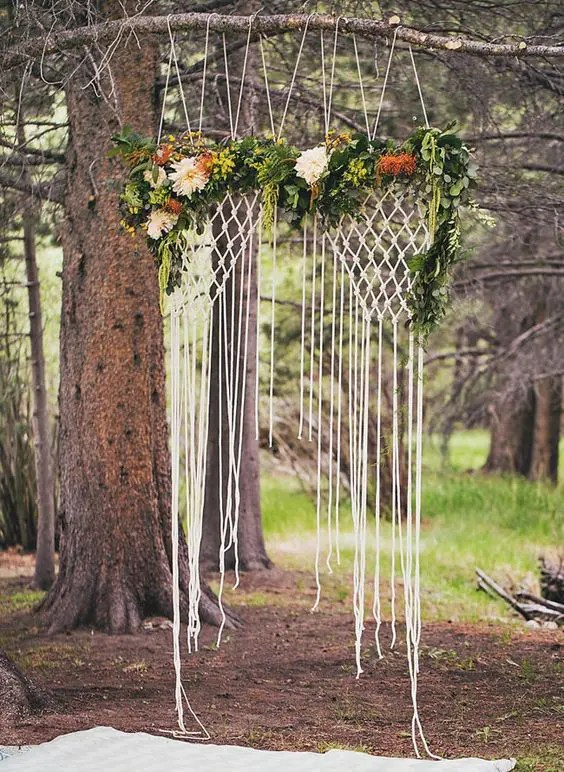 hanging macrame backdrop with flowers looks ethereal
