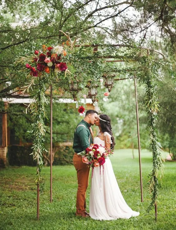 a metal construction with lanterns, greenery and bold flowers