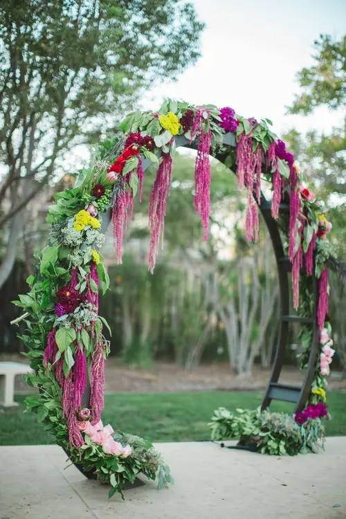 rounded wedding arch decorated with greenery and bold flowers for a boho look