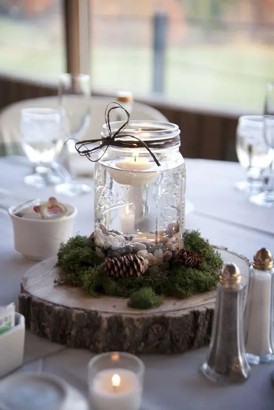 15 more gorgeous winter wedding centerpieces crazyforus a wooden slice with a jar with a flowing candle moss and pinecones for a junglespirit Images