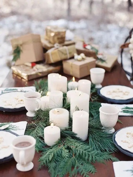 a simple evergreen runner and pillar candles on it for a modern winter wedding