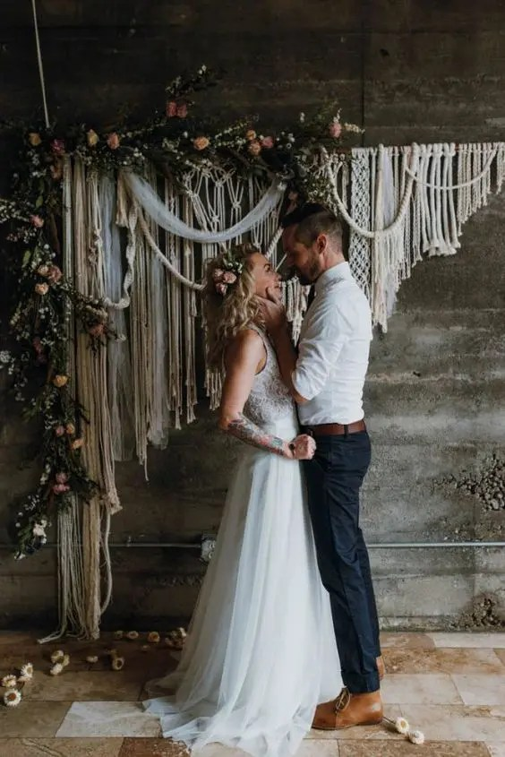 a macrame wedding backdrop with greenery and blush blooms for a boho wedding
