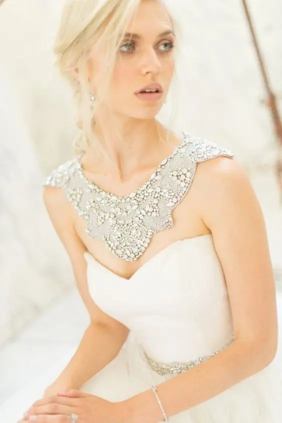 a chic jewelry piece in between a necklace and a shoulder piece with lots of rhinestones
