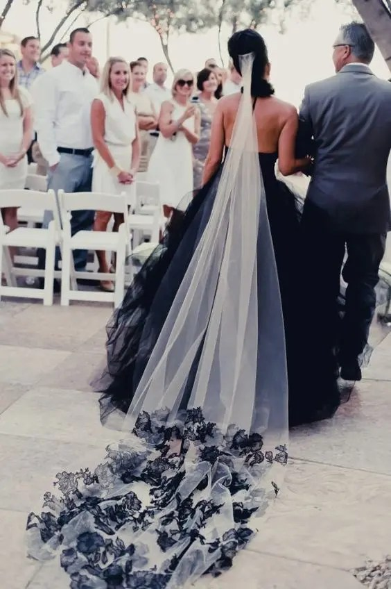 a black and white long veil with a train that matches the dress
