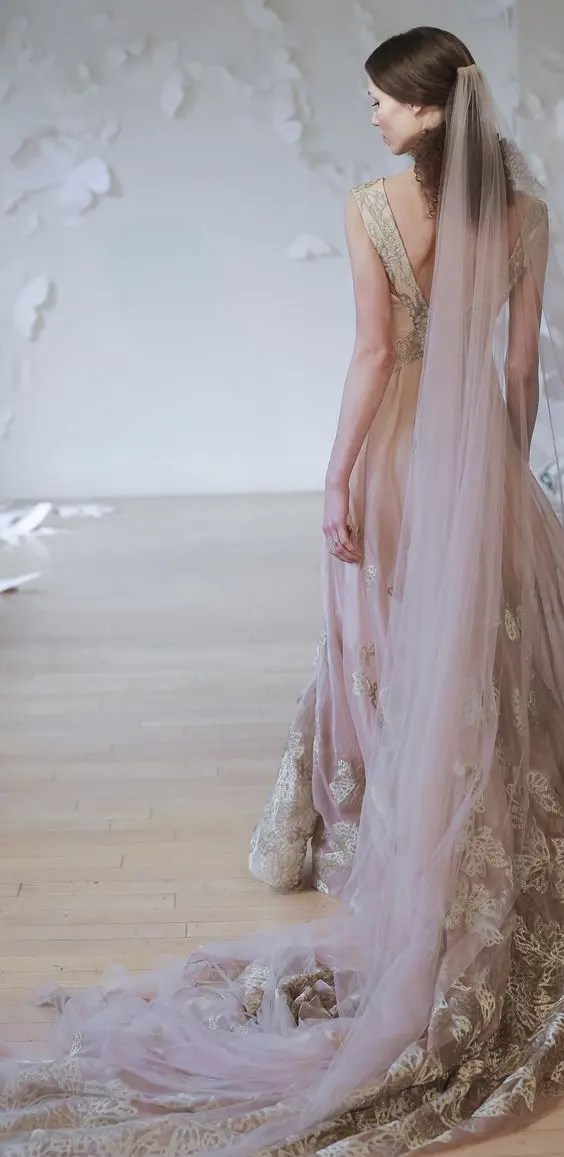 a bride rocking a pink and gold lace wedding gown and a pink veil
