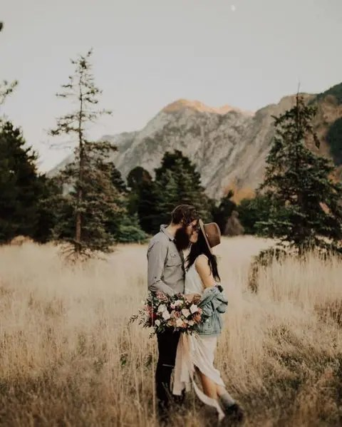 a denim jacket and a brown hat plus booties for a boho forest or woodland elopement