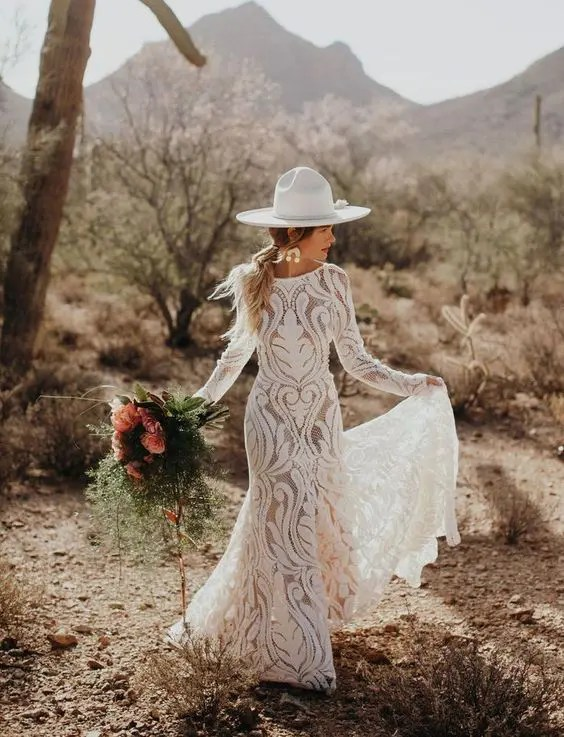 a boho desert bride wearing a cool white hat with white blooms that wows