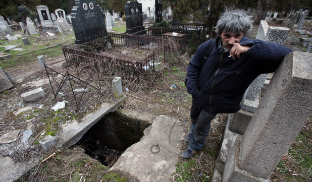 Homeless Bratislav Stojanovic is seen near the grave where he now dwells in a cemetery in the city of Nis, Serbia